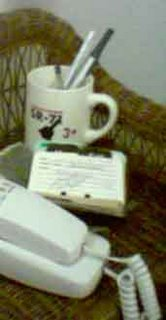 [still entropic life on bedside table; note 'SR-71' mug holding pens (also note rolodex)]